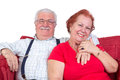 Good natured senior couple relaxing together in a close embrace looking at the camera with charming friendly smiles Stock Images