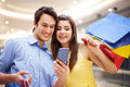 Good news smiling couple checking something on the mobile phone Royalty Free Stock Photo