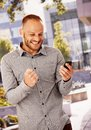 Good news young man standing outdoors with clenched fist looking at mobilephone happy reading Royalty Free Stock Image