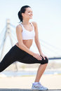 Good place for exercising beautiful woman doing her outdoor exe exercises with a bridge on the background Stock Images