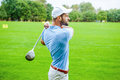 Good strike side view of confident golfer swinging his driver and looking away while standing on golf course Royalty Free Stock Photography