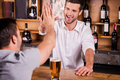 It is good to see you again rear view of male customer talking bartender while sitting at the bar counter Stock Photo