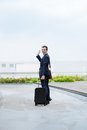 Goodbye cheerful businessman with a suitcase waving and looking at the camera Stock Photo