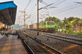 Goods train passes a deserted Indian railway station.