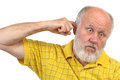Goofy bald senior mans picking his ear Stock Image