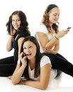 Goofy phone girls three young teen friends texing or on the the one on the floor is acting especially on a white background Royalty Free Stock Photos