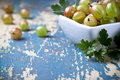 Gooseberries in bowl with leaves on old table background copy space Stock Images