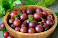 Gooseberries in wooden bowl on table Royalty Free Stock Photo