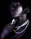 Gorgeous african woman closeup portrait of isolated on black background elegant white pearl beads stylish makeup luxury beauty Stock Photos