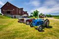 Gorgeous amazing front side view of classic vintage retro tractors standing near the farm building Royalty Free Stock Photo