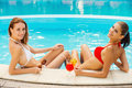 Gorgeous beauties at the pool rear view of two beautiful young women in bikini looking over shoulder and smiling while relaxing Royalty Free Stock Images