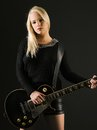 Gorgeous blond playing electric guitar photo of a sexy female a black Stock Image