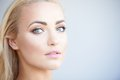 Gorgeous blond woman with beautiful green eyes turning to look at the camera a serious expression and parted lips close up of Royalty Free Stock Photos