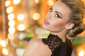Gorgeous blond woman at a party closeup portrait of beautiful in stylish black dress looking back the camera over her Royalty Free Stock Photo