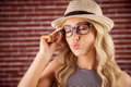 Gorgeous blonde hipster sending air kiss against red brick background Stock Image