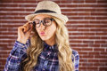 Gorgeous blonde hipster sending air kiss against red brick background Stock Photo