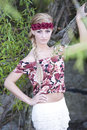Gorgeous blonde wearing flower crown a young girl looking at the camera while a red with a white skirt and flowery top in a forest Royalty Free Stock Photography