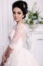 Gorgeous bride with dark hair in luxuious wedding dress