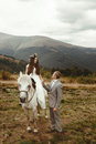 Gorgeous bride riding a white horse and stylish groom,  boho wed Royalty Free Stock Photo
