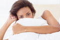Gorgeous brunette covering face with pillow at home in the bedroom Royalty Free Stock Image