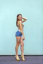 Gorgeous brunette girl with freckles a beautiful makeup in fashionable clothes: a gold shoes, top, and small jeans shorts