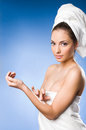 Gorgeous brunette spa  woman using moisturizer. Stock Image