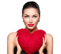 Gorgeous brunette woman with heart shaped red pillow Royalty Free Stock Photo
