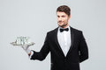 Gorgeous butler in tuxedo standing and holding tray with money Royalty Free Stock Photo
