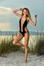 Gorgeous Caucasian girl with slim fit body in black swimsuit enjoying summer time. Royalty Free Stock Photo
