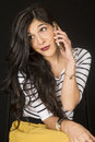 Gorgeous dark model sitting talking on her cell phone Royalty Free Stock Photo