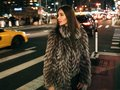 Gorgeous elegant woman walking on night city street wearing fake fur jacket and holding bag looking to the side. Royalty Free Stock Photo