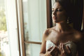 Gorgeous exotic french bride in white dress posing near window c Royalty Free Stock Photo