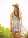 Gorgeous girl walking in the field summer lifestyle happy carefree woman wearing stylish sun dress Stock Photos
