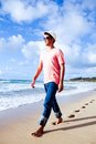 Gorgeous guy walking along kealia beach kauai good looking man on the sand in hawaii Royalty Free Stock Photo