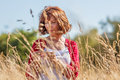 Gorgeous middle aged woman wandering in dry high meadows outdoors relaxation enjoying quietness summer daylight Royalty Free Stock Image
