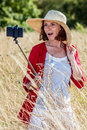 Gorgeous 50s woman making a selfie on mobile phone on stick Royalty Free Stock Photo
