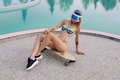 Gorgeous girl with blond hair in elegant bikini relaxing beside swimming pool Royalty Free Stock Photo