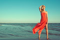 Gorgeous slim blond model in red strapless dress with flying train standing on tiptoe in the sea water Royalty Free Stock Photo