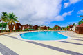 Gorgeous, stunning view of hotel grounds with cozy, comfortable swimming pool located near the beach area on sunny day Royalty Free Stock Photo