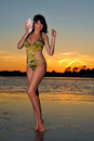Gorgeous swimsuit model standing on the ocean coastline during sunset time and holds in one s hand big seashell Royalty Free Stock Photography