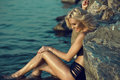 Gorgeous tanned sexy smiling blonde sitting in the water leaning her back on large stones, her hand on the leg Royalty Free Stock Photo