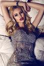 Gorgeous woman with blond hair in elegant dress lying on divan Royalty Free Stock Photo
