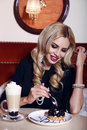 Gorgeous woman with blond hair sitting in cafe with coffee and dessert fashion interior photo of sexy elegant suit glass of sweet Royalty Free Stock Photography