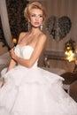 Gorgeous woman with blond hair wears luxurious wedding dress and bijou fashion studio photo of bride in Stock Photos