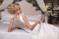 Gorgeous woman with blond hair wears luxurious wedding dress and bijou Royalty Free Stock Photo