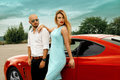 Gorgeous woman and handsome man with red sport car Royalty Free Stock Photo