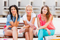 Gorgeous women out in town three beautiful the city sitting on a bench and smiling Royalty Free Stock Photography
