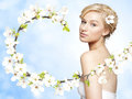 Gorgeous young blond woman spring flower branch bright blue background Royalty Free Stock Photo
