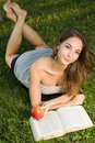 Gorgeous young brunette outdoors with her book. Royalty Free Stock Image