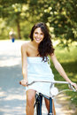 Gorgeous young girl with her cycle in park Royalty Free Stock Photography